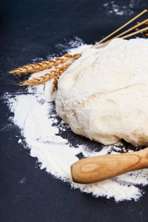 Photo for Baking background with flour, rolling pin and grain ears on black chalkboard - Royalty Free Image