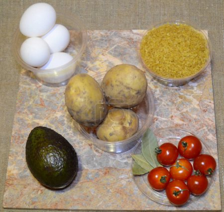 ingredients for instant cooking of an interesting dish: eggs, potatoes, bulgur, avocado, cherry tomatoes, bay leaf