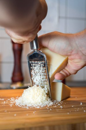 man grating parmesan cheese on wooden cutting board , close-up