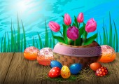 Postcard with tulips in a wicker basket Easter eggs and cupcakes on a wooden table against the background of grass and sky