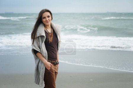 Autumn lifestyle fashion portrait of young stylish hipster woman walking on a sea beach, wearing cute trendy outfit, enjoy weekends and travel