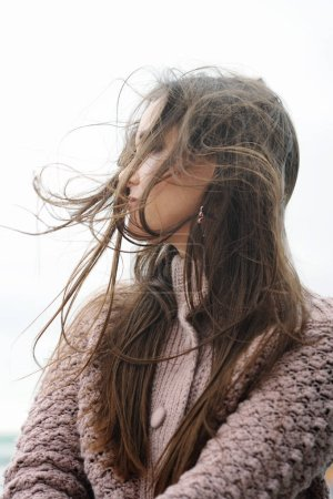 Photo for Beautiful smiling brunette woman profile portrait, chic long hair fluttering in the wind, soft focus - Royalty Free Image