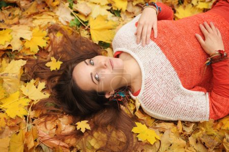 Smiling happy womanl portrait, lying in autumn leaves