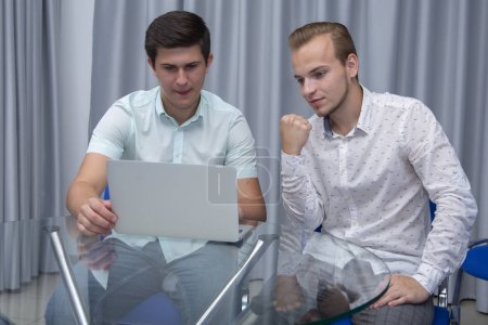 Photo for Two cheerful young businessmen working and using laptop on business meeting together. Portrait - Royalty Free Image