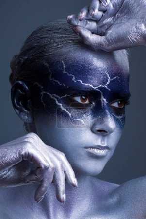 Photo for Young woman with lightning face art on black background. Female lightning design body art. Blue silver face art. - Royalty Free Image