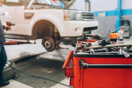 Photo pour Service d'entretien de réparation automobile avec des outils vintage. Voiture soulevée sur l'ascenseur de voiture dans le garage de service automobile - image libre de droit