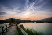 a lake bridge at sunset