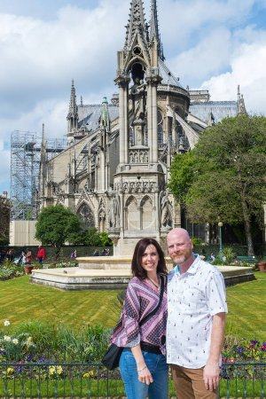 A man and a woman pose for a photo in front of Notre-Dame Cathed
