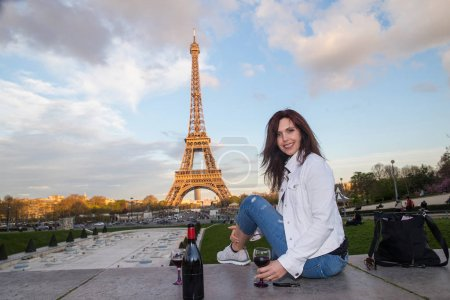 Beautiful woman drinking wine at the Eiffel Tower in Paris, Fran