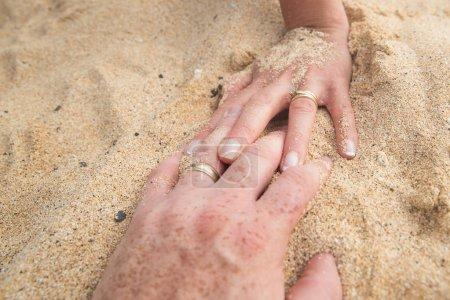 Holding hands on a sandy beach