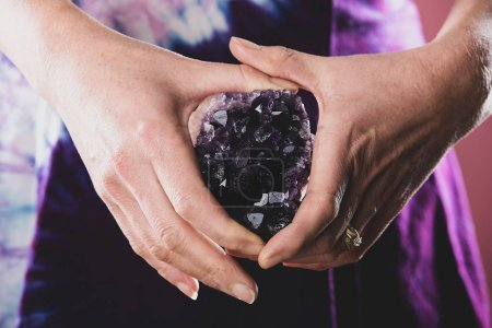 Holding a purple amethyst crystal