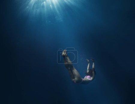 Girl sank in blue deep water of ocean, against dar...