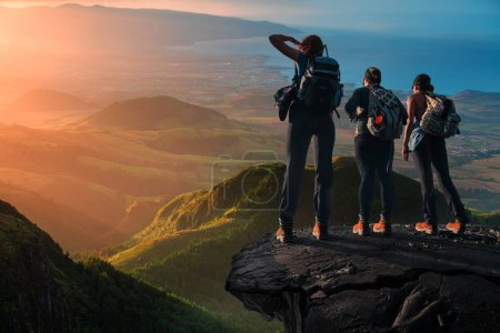 Photo for Three girls watching sunset standing on hike, beautiful landscape - Royalty Free Image