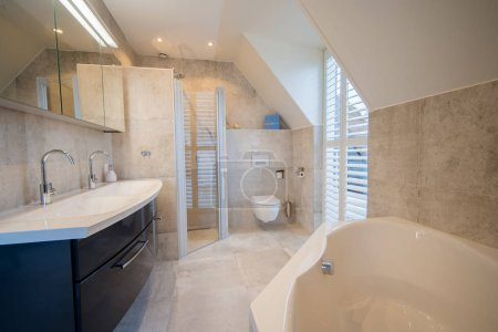 Baño construido arquitectónicamente con baldosas de lujo, persiana blanca