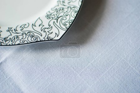 Porcelain plate with decorative border on white tablecloth