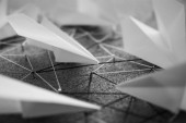 Group of white paper planes over the threads linking the nails. Entities connected. Abstract concept (idea) of airlines, freedom, leadership, communication, network and teamwork.