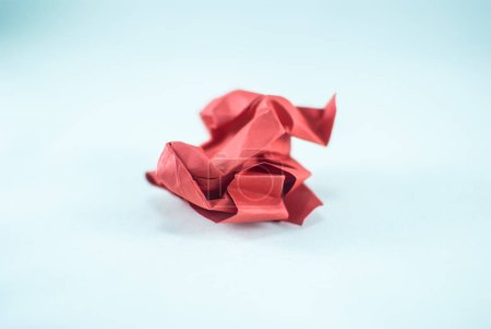 Crumpled red paper on light background
