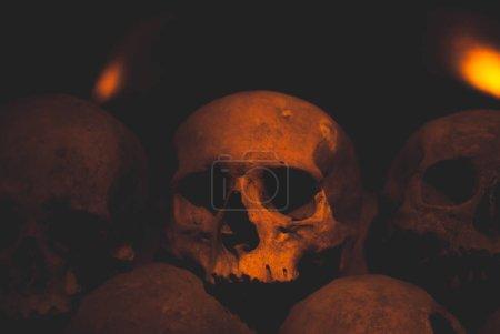 Großaufnahme eines Schädels, übersät mit Spinnennetz und Staub in den Katakomben. Zahlreiche gruselige Totenköpfe in der Dunkelheit im Kerzenschein. abstraktes Konzept, das Tod, Terror und das Böse symbolisiert.