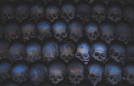 Schädel, die mit Spinnennetz und Staub in den Katakomben bedeckt sind. Zahlreiche gruselige Totenköpfe im Dunkeln im Kerzenschein. abstraktes Konzept, das Tod, Terror und das Böse symbolisiert. Vintage-Retro-Farben