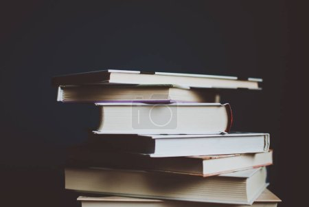 Tower of colorful books on the table. Closeup of pages. Abstract concept of knowledge, education, learning, and literature. Filter