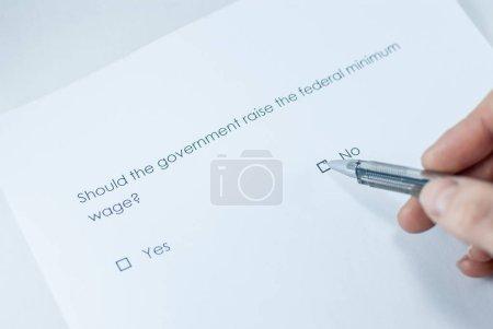 Foto de ¿Pregunta encuesta: debería el gobierno elevar el salario mínimo federal? Respuesta: No. - Imagen libre de derechos