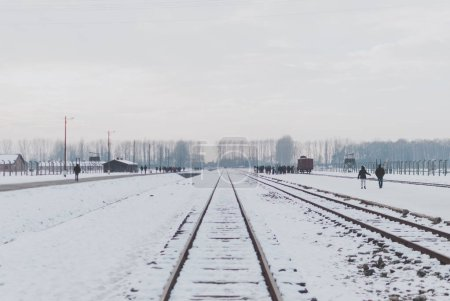 Oswiecim, Poland - February 16, 2018: Railway tracks of Auschwitz concentration camp,  watchtowers, and visitors