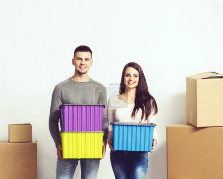 Man and woman moving in a new house. Loving couple in a new home. People with a boxes.