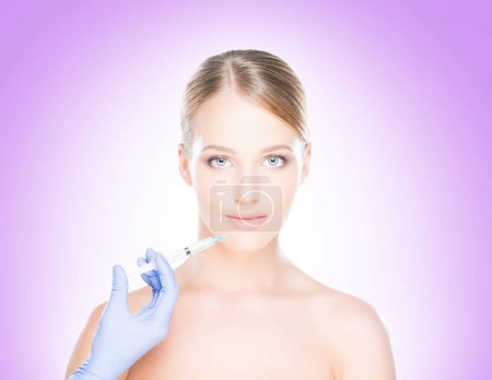 Young, beautiful and healthy woman having skin injections over magenta background. Plastic surgery concept.