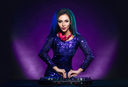 Photo pour Fille jeune, séduisante et belle et sexy dj jouant de la musique sur une soirée disco dans une boite de nuit - image libre de droit