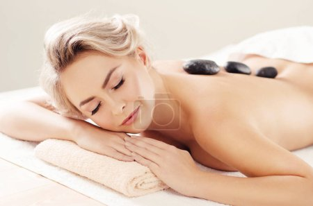 Beautiful and healthy blonde woman getting spa therapy and massaging treatments. Recreation and healthcare concept.