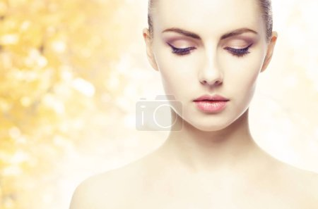 Photo for Portrait of young, natural and healthy woman over yellow autumn background. Healthcare, spa, makeup, skin care and face lifting concept. - Royalty Free Image