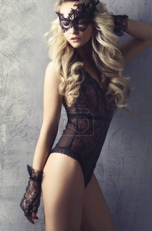 Close-up photo of young blonde woman posing in sexy lingerie. Girl in mask and beautiful underwear.