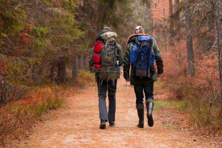 Deux gars barbus avec des sacs à dos de randonnée en forêt. Camp, aventure, voyage et concept de pêche