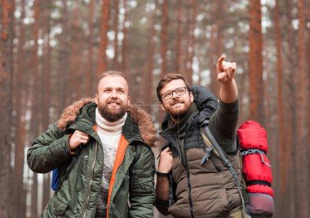 Homme avec un sac à dos et son ami avec une barbe de randonnée en forêt. Camp, aventure, voyage concept