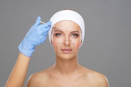 Doctor injecting in a beautiful face of a young woman. Plastic surgery, skin lifting and aesthetic medicine concept.
