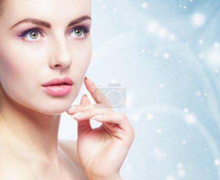 Photo pour Portrait de jeune, belle et saine femme sur fond de Noël d'hiver. Soins de santé, spa, maquillage et lifting du visage concept . - image libre de droit