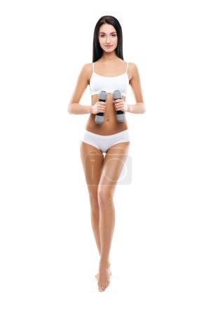 Jeune fille sportive et en forme pompage un haltère isolé sur blanc. Sport, fitness et mode de vie sain concept .