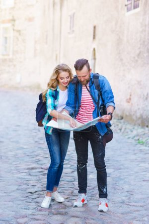 Photo for Young travelers exploring directions with a tourist map. Man and woman having vacation. Backpackers, traveling and tourism concept. - Royalty Free Image