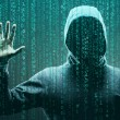 Computer hacker in mask and hoodie over abstract b...