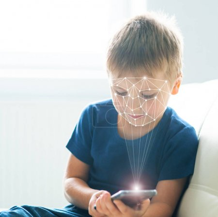 Little boy using face id authentication. Kid with a smartphone. Digital native children, internet and gadgets concept.