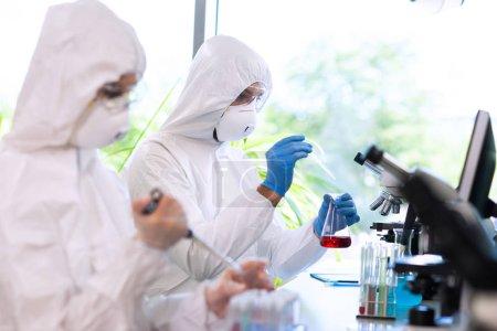 Photo pour Scientifiques en combinaisons de protection et masques travaillant dans un laboratoire de recherche utilisant des équipements de laboratoire : microscopes, éprouvettes. Concept de médecine, d'infection et de découverte de vaccins. - image libre de droit