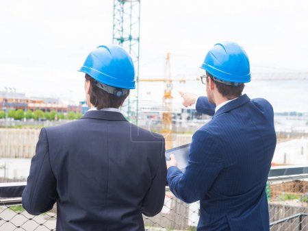 Photo for Real estate developers in helmets. New office construction. Confident business men and architect talking in front of modern office building. Businessman and his colleague have conversation. - Royalty Free Image