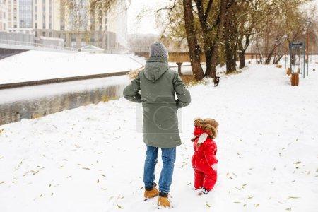 Photo pour Jeune femme méconnaissable en tenue décontractée d'hiver marchant avec son enfant en bas âge dans un parc enneigé près de Rver, pleine hauteur - image libre de droit