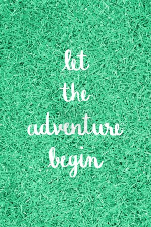 Photo for Let the adventure begin hand lettering on green grass field. - Royalty Free Image