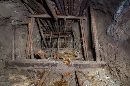 Underground abandoned iron ore mine tunnel with collapsed wooden timbering
