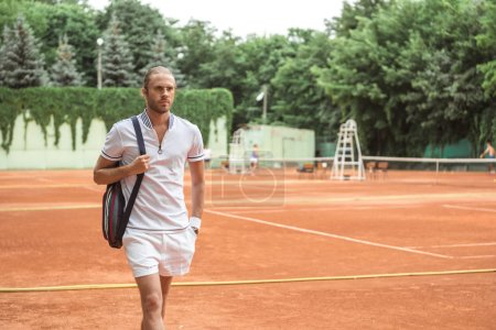 handsome tennis player after training on brown tennis court