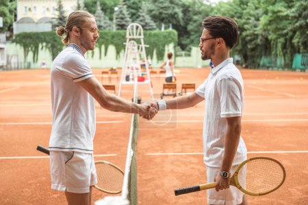 old-fashioned tennis players with wooden rackets shaking hands after game on court
