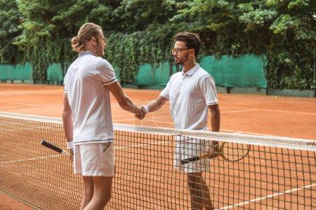 Photo pour Joueurs de tennis athlétique avec des raquettes en bois, se serrant la main après match sur Cour - image libre de droit