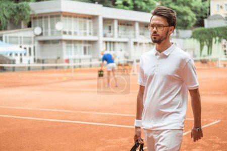 Photo pour Beau rétro style tennisman après l'entraînement sur un court de tennis - image libre de droit