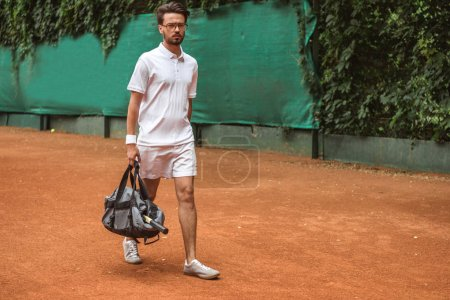 Photo for Handsome tennis player walking with bag after training on tennis court - Royalty Free Image